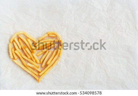 The symbols of the heart is lined with french fries on kraft paper. Poor street food, obesity, heart disease. French fries #534098578