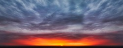 The symmetrical epic sky with a bright flash of the sun among the black clouds at sunset is a high-resolution panoramic shot