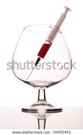 The syringe with narcotic in empty wineglass