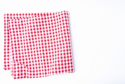 The tablecloth checkered red and white fabric cotton folded place on a white table with copy space. Background for designing food and beverage menus in restaurants.