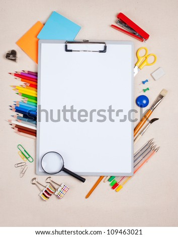 The tablet of paper and school supplies - stock photo