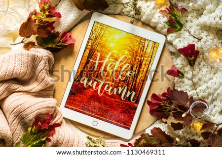 The tablet says the word hello Autumn with red leaves and a dais on the wooden background. Concept of the autumn View from above. Copy Space. #1130469311