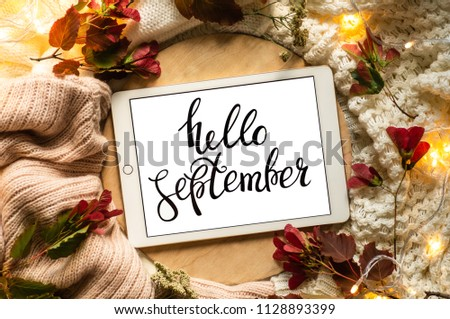 The tablet says the word hello September with red leaves and a dais on the wooden background. Concept of the autumn View from above. Copy Space. #1128893399