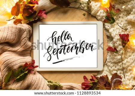 The tablet says the word hello September with red leaves and a dais on the wooden background. Concept of the autumn View from above. Copy Space. #1128893534