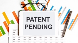 The tablet with tex Patent Pending on business charts and pen,business