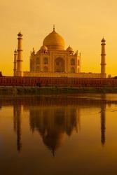The Taj Mahal reflecting in the Yamuna river at sunset.