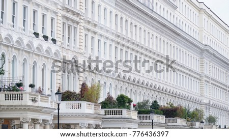 The tall facade of a section of terraced Georgian housing in an expensive part of London, UK