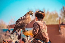 The tamer of the predatory eagle holds his bird in his arms. Falcon hunting.