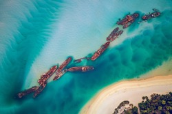 The Tangalooma Wrecks used to be 15 steam driven barges which were deliberately sunk in 1963 along the Moreton Island coastline to form a breakwall so that small boats can anchor in shelter.