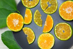 The tangerine sliced is placed in a black dish and the edge of the dish has green orange leaves.