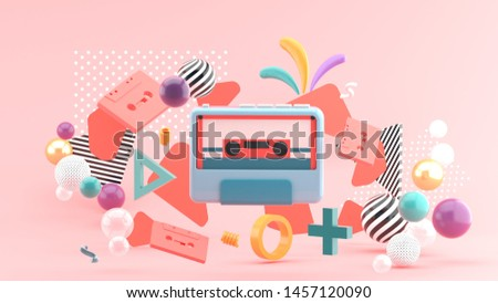 The tape player is surrounded by colorful tape and balls on a pink background.-3d rendering.
