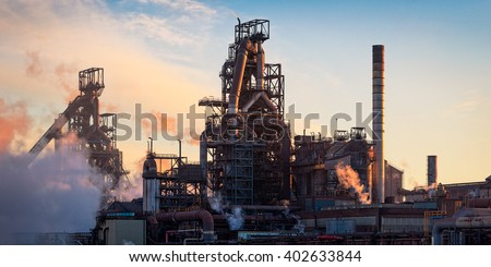 The Tata Steel plant at Port Talbot, South Wales.  Sunset light emphasizing the structures of the plant like pipes and smoke/steam emissions.