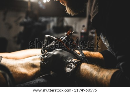 The tattoo artist creates a picture on the body of a man. close-up of tattoo machines and hands