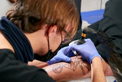 the tattoo artist in blue gloves doing a tattoo on the leg of a male in a studio