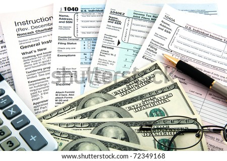 The tax forms with the glasses, money and the pen.
