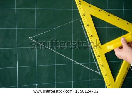 The teacher draws a triangle. Yellow triangle. Geometric problem. School board Mathematics, geometry. #1360124702