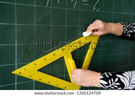 The teacher draws a triangle. Yellow triangle. Geometric problem. School board Mathematics, geometry. #1360124708