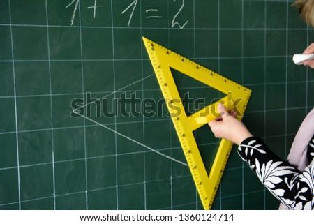 The teacher draws a triangle. Yellow triangle. Geometric problem. School board Mathematics, geometry. #1360124714