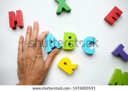 The teacher tells what are the letters and shows a wooden toy letter on a white background. learn the alphabet. Man's hand takes the symbol . ABC game #1476800591