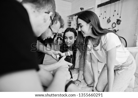 The team of photographers showing pictures on screen of camera for twins models girls on studio. Professional photographer on work.