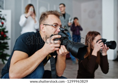 The team of two photographers shooting on studio behind another three workers. Professional photographer on work. Master class.