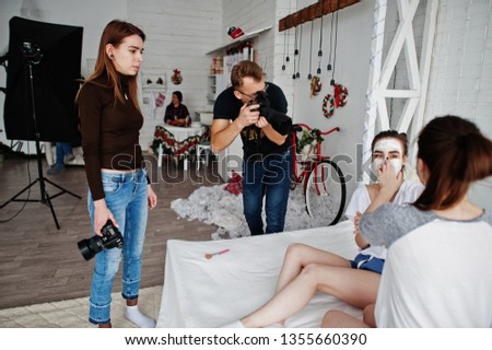 The team of two photographers shooting on studio twins girls while they make their own masks cream. Professional photographer on work.