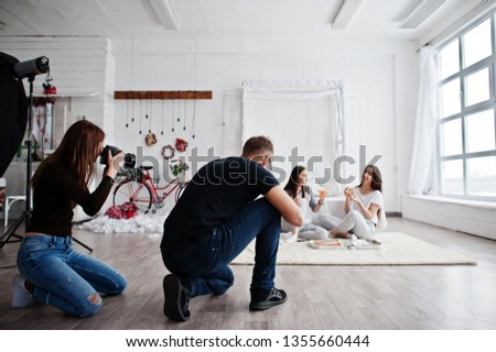 The team of two photographers shooting on studio twins girls who are eating pizza. Professional photographer on work.