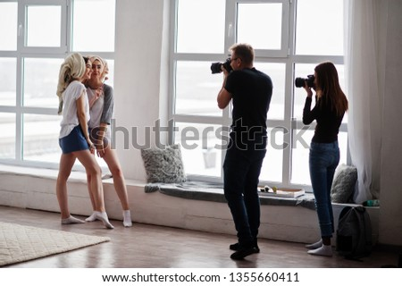 The team of two photographers shooting twins models girls on studio against large windows. Professional photographer on work.
