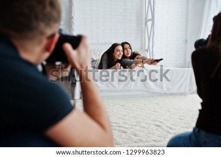 The team of two photographers shooting twins models girls while they click the remote control from the TV on studio. Professional photographer on work.