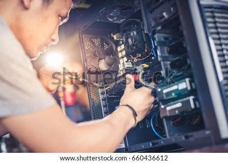 The technician hold the screwdriver for repairing the computer. the concept of computer hardware, repairing, upgrade and technology.