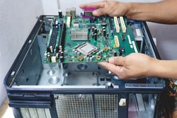 The technician holds a board computer pc for the upgrade to repair inside The socket motherboard or equipment. Computer upgrade center concept