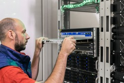 The technician installs a new server board in the ISP's central router. Updating the hardware part of the data center server room.