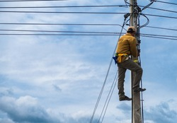 The technician is climbing on the electric pole for repairing electric problems in the background of cloudy blue sky, concept of risk for hazardous work.