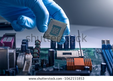 The technician is laying a CPU on the socket of the computer motherboard. the concept of computer, service, electronics, hardware, repairing, upgrade and technology. #1062151853