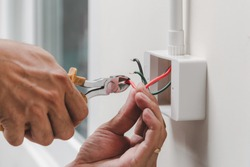 The technician is using a pliers wrench to install the power plug on the wall.