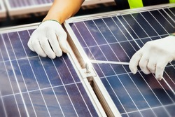 The technician's hand uses an Allen key to tighten it during installation to the structure to ensure the strength and durability of the solar panel.