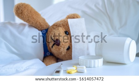 The teddy bear and the fever-reducing patch lie on the bed in a white-tone bed next to a medicine table and body temperature monitor. Used for health insurance or illness concepts