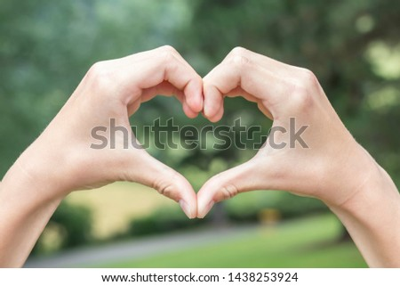 The teenager and the girl folded their hands in the shape of a heart against the background of a coniferous forest on a sunny day. The concept of joy and happiness in harmony with nature #1438253924