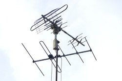 The television aerial or antenna to receive a network in background of white in the sky .