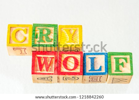 The term cry wolf visually displayed on a white background using colorful wooden toy blocks image with copy space in landscape format
