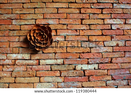 The terracotta flower on the brick wall #119380444