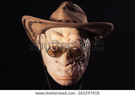 the terrible head of the goblin in round points and a cowboy\'s hat on a black background