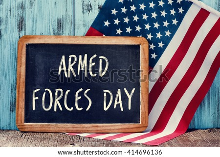 the text armed forces day written in a chalkboard and a flag of the United States, on a rustic wooden background