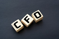 the text CFO is written on wooden cubes on a bright blue surface. In the background are rows of cubes with different letters. Business concept. CFO - short for chief financial officer