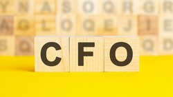 the text CFO is written on wooden cubes on a bright yellow surface. In the background are rows of cubes with different letters. Business concept. CFO - short for chief financial officer
