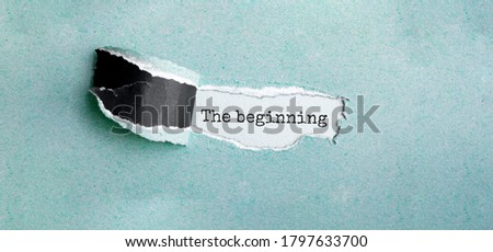 The text The beginning appearing behind torn brown paper Stockfoto ©