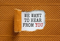 The text 'we want to hear from you' appearing behind torn brown paper. Beautiful background. Business concept.