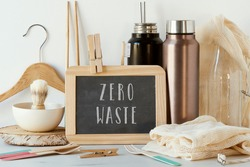 the text zero waste in a chalkboard and a pile of no-plastic sustainable items, such as metal water bottles, a glass bottle, shopping mesh bags or reusable wooden cutlery and chopsticks