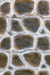 The texture and background of the wall made of old stone with outlined edges imitating the stylized marsh-colored snake skin are made in the form of a homogeneous cobblestone masonry. Vertical image.