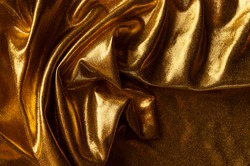 The texture and drapery of the golden fabric of the festive dress. Abstract golden background from fabric draped with waves.